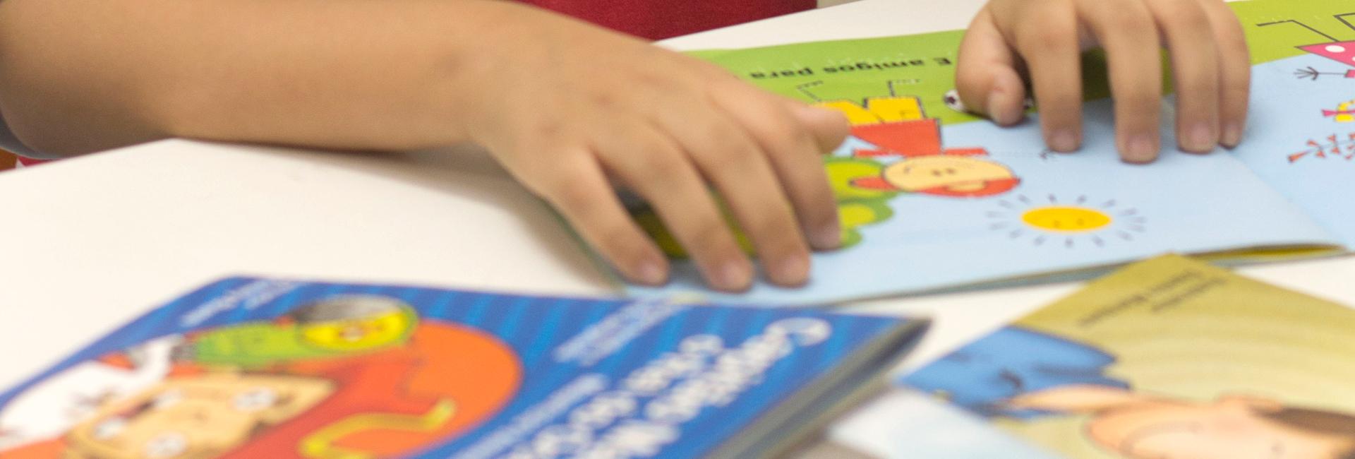 Foto das mãos de uma criança lendo um livro em braile, ao redor há mais livros.
