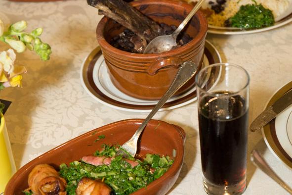 Imagem de destaque: mesa com cumbuca de feijoada, couve com torresmo e um copo de refrigerante.