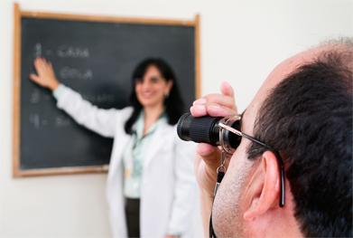 Foto de um homem com baixa visão utilizando um equipamento para ler um quadro negro à distância. Uma profissional da fundação Dorina o auxilia.