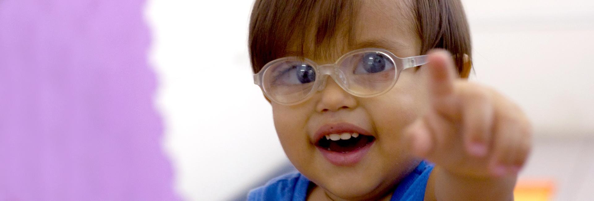 Foto de uma criança com baixa visão sorrindo e apontando com o dedo indicador.