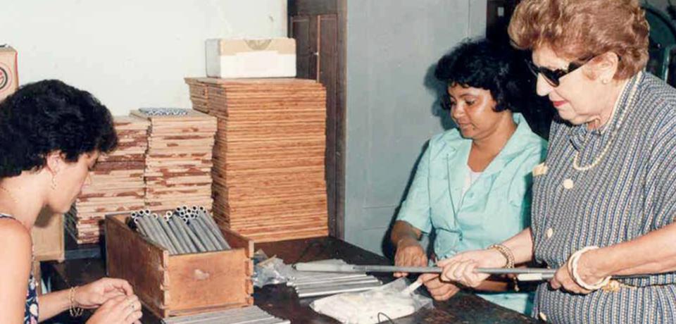 Foto de Dorina Nowill auxiliando na montagem de bengalas retráteis.