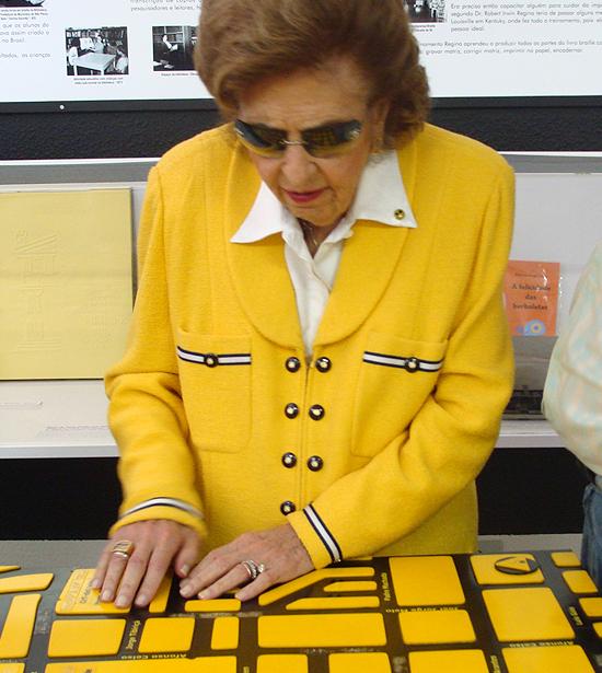 Foto de Dorina Nowill tocando em um mapa tátil das redondezas da sede da Fundação.