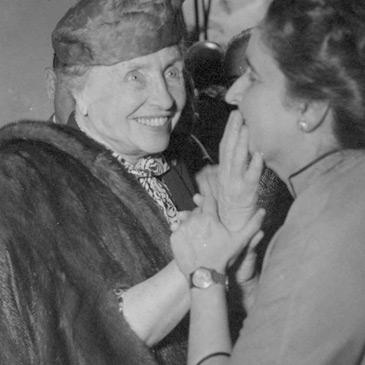 Foto em preto e branco de Hellen Keller tocando o rosto de Dorina Nowill.
