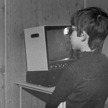 Foto em preto e branco de um menino usando óculos escuro em frente a uma tela.