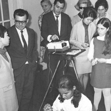 Foto em preto em branco de pessoas em volta de um projetor na inauguração do serviço de reabilitação.