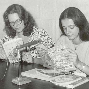 Foto em preto em branco de duas mulheres sentadas. À frente delas há uma mesa com um microfone e livros