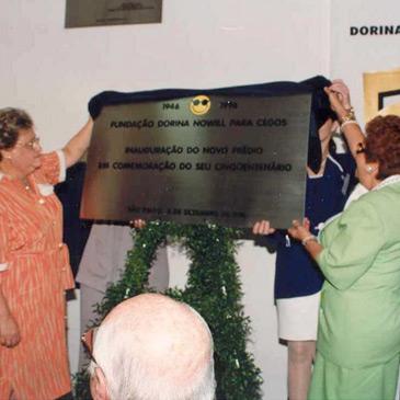 Foto de Dorina Nowill e uma outra senhora tirando a cobertura de uma placa de metal que inaugura o novo prédio.