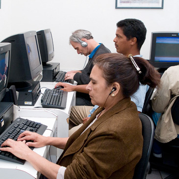 Foto de alunos de cursos da fundação Dorina utilizando computadores.