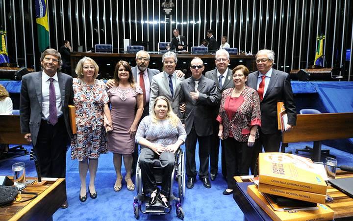 Foto de um grupo de Pessoas na câmara dos Deputados. Há pessoas em pé usando roupas sociais e sorrindo para a câmera.