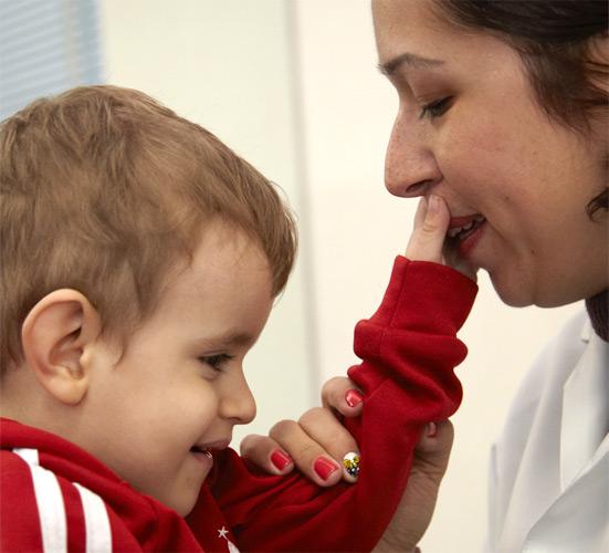 Foto de um atendimento realizado na fundação Dorina. Uma criança pequena toca o rosto da fisioterapeuta e sorri.
