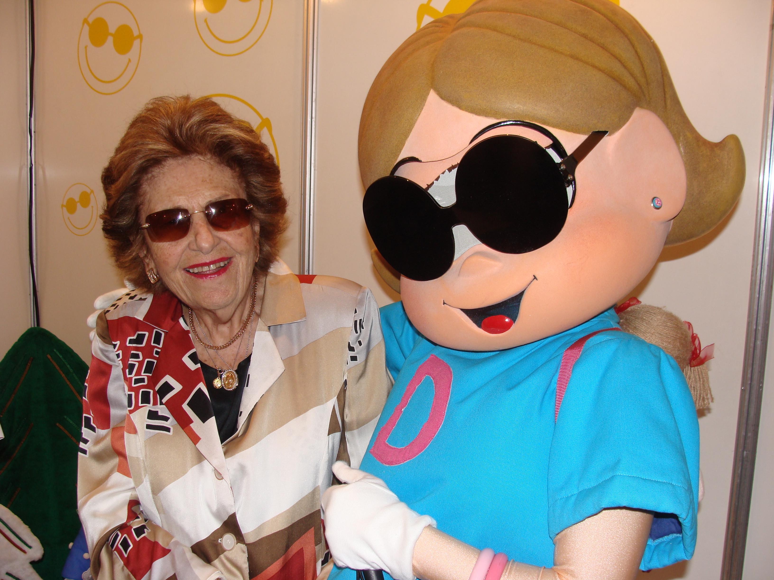 Foto de Dorina Nowill, com Dorinha, personagem da Turma da Mônica feita em sua homenagem.