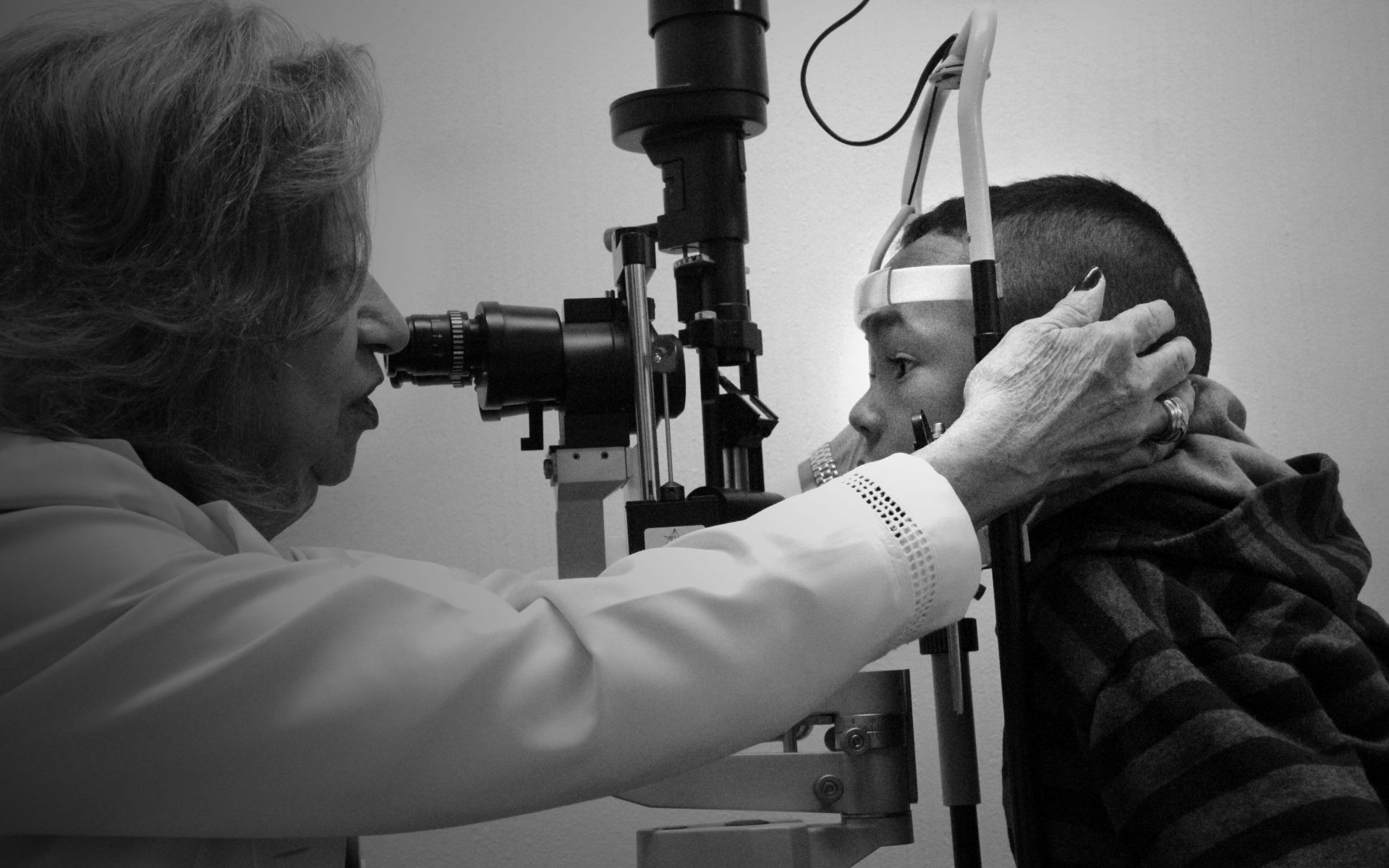 Foto de uma ortopedista da Fundação Dorina examinando um garoto com um aparelho.