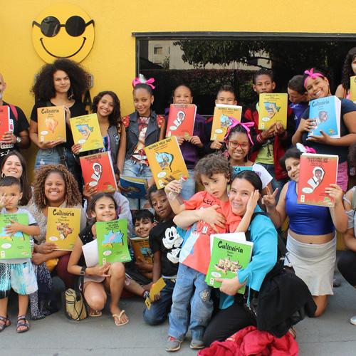 Descrição da imagem: foto de um grupo de crianças e adultos segurando livros de capas coloridas. Eles olham pra frente e sorriem.
