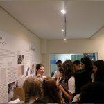 Foto de uma guia da fundação Dorina apresentando a o centro de memória para um grupo de meninas.