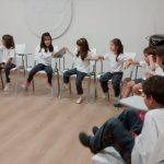 Foto de um grupo de crianças sentadas formando um semicírculo, em uma da pontas está uma responsável fazendo sinal de silêncio.