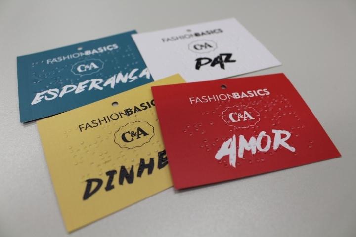 Foto de quatro cartões: um azul escrito esperança, um branco escrito Paz, um amarelo escrito Dinheiro, e um vermelho escrito Amor, todos em tinta e Braile.