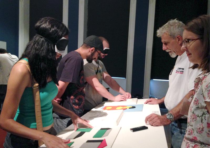 Descrição da imagem: foto de cinco pessoas ao redor de uma mesa no Museu Nacional de Belas Artes, no Rio de Janeiro. Duas delas usam vendas nos olhos e tateiam objetos geométricos em relevo na mesa. Fim da descrição.