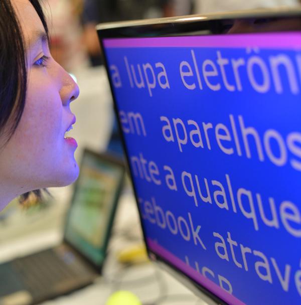 Descrição da imagem: foto de Marina lendo um texto em um monitorcom fonte ampliada . Ela está de perfil, com o rosto bem próximo à tela. Fim da descrição.
