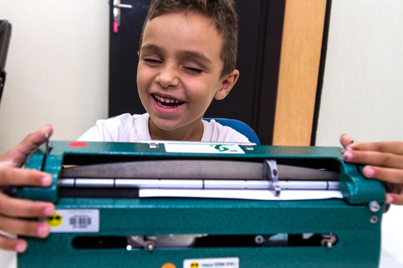 Descrição da imagem: foto de Bryan com as duas mãos sobre uma máquina de escrever em braille. Ele está de frente, sorrindo com os olhos fechados.