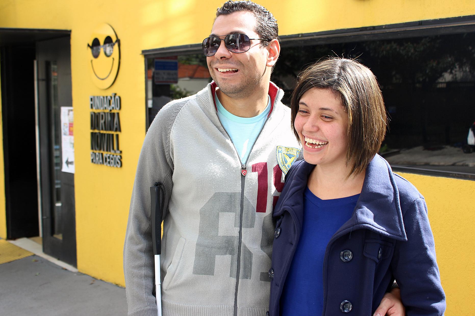Descrição da imagem: foto de Felipe e Juliana na calçada da Fundação Dorina. Eles são retratados da cintura pra cima, em meio perfil, abraçados e sorrindo. Ao fundo vemos a porta de entrada da Fundação Dorina com o logotipo da instituição numa parede amarela. Fim da Descrição.