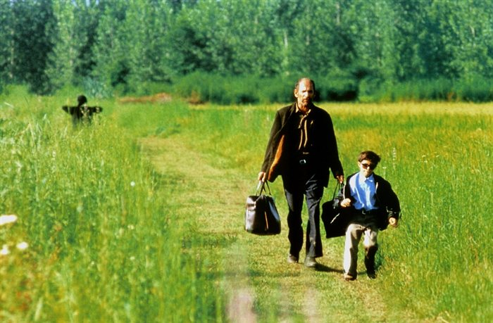 Descrição da imagem: cena do filme A cor do paraíso. Um homem e um menino caminham por uma estrada verdejante. Eles estão de frente. O homem carrega duas malas. O menino usa óculos escuros e caminha ao seu lado. Fim da descrição.