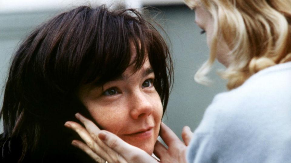 Descrição da imagem: cena do filme Dançando no Escuro. Uma moça de cabelos castanhos sorri e olha para outra de cabelos loiros, que toca seu rosto com as duas mãos. Fim da descrição.