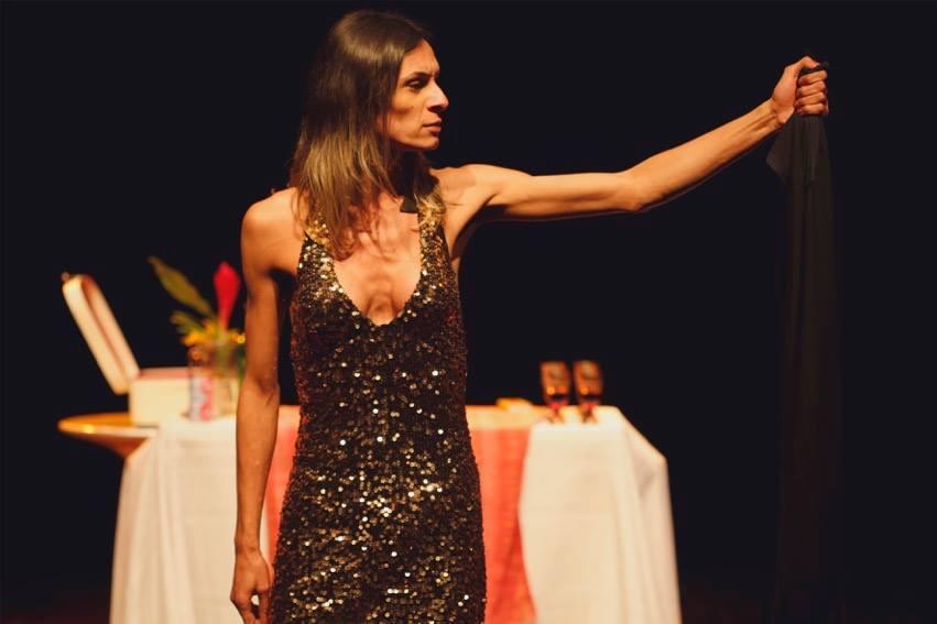 Descrição da imagem: foto da atriz Renata Carvalho segurando um pano preto. Ela está de frente, olhando para o lado, com o braço esquerdo aberto e levantado na altura do rosto.A atriz usa um vestido de festa brilhante. Ao fundo há uma mesa com toalha branca e vermelha. Fim da descrição.