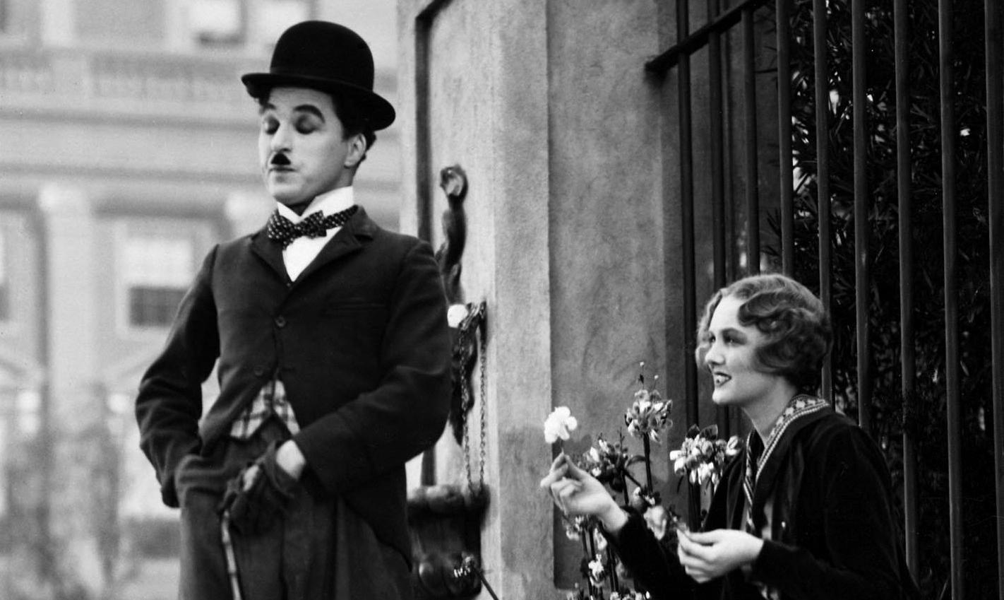 Descrição da imagem: cena em preto e branco dos dois personagens principais de As Luzes da Cidade. É dia e eles estão numa calçada. O homem veste um fraque velho, gravata borboleta e chapéu-côco. A jovem florista cega está à direita, de perfil. Ela segura uma flor com a ponta dos dedos e sorri. Fim da descrição.