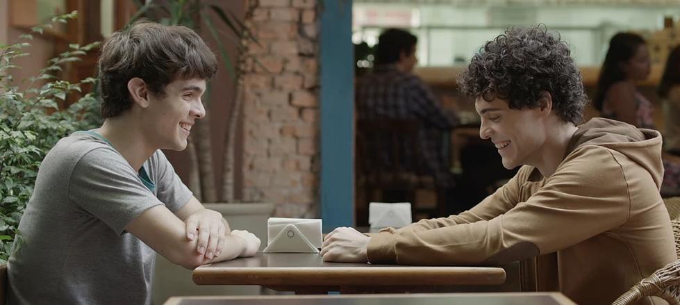 Descrição da imagem: cena do filme Hoje eu quero voltar sozinho. Dois adolescente conversam em uma mesa. Eles estão sentados de frente para o outro, de perfil e sorrindo. Fim da descrição.