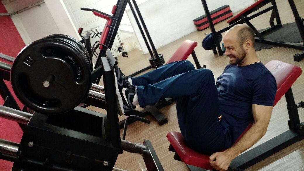 Descrição da imagem: foto de Jefferson levantando peso com as pernas em um aparelho de academia. Ele usa roupas esportivas e tem uma expressão de esforço físico.