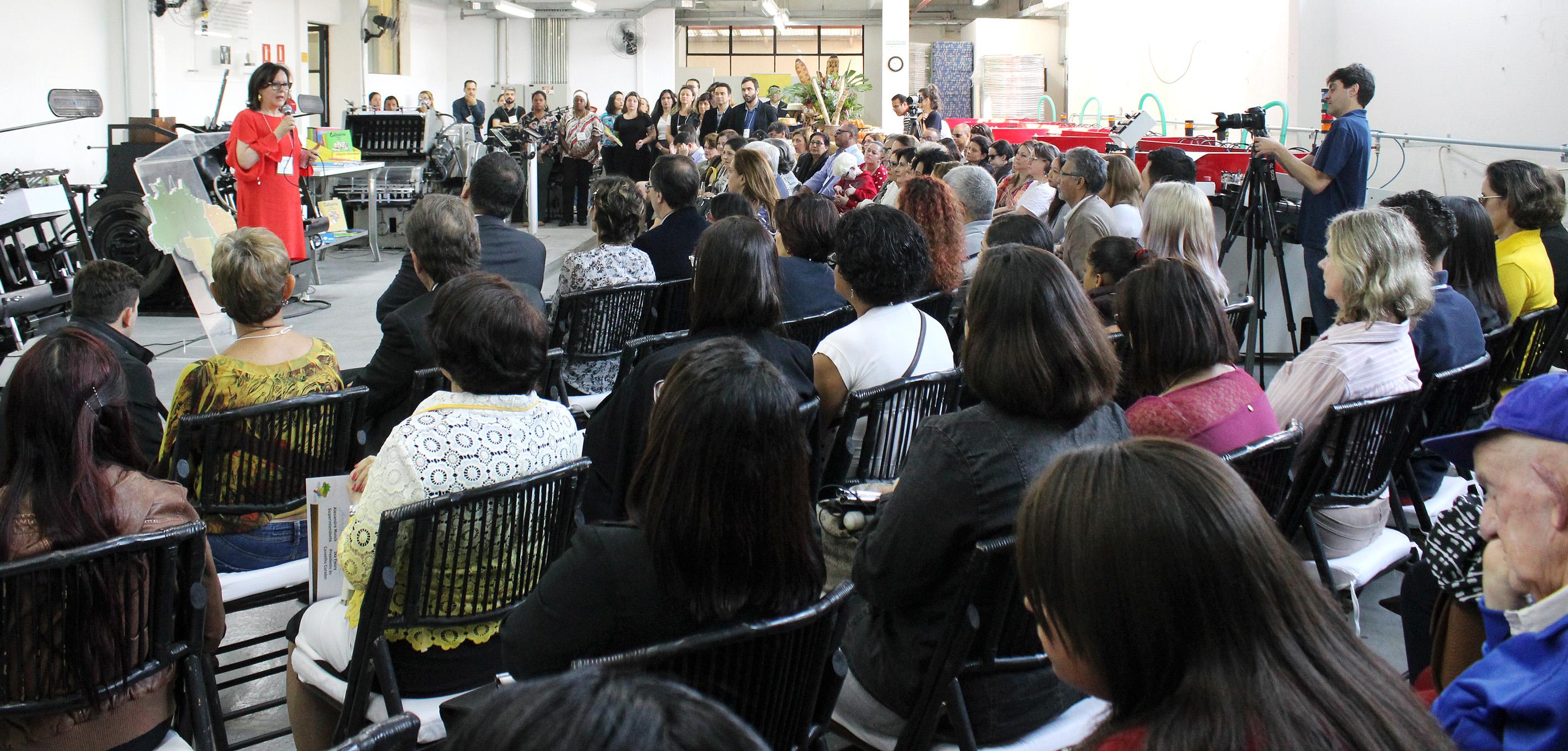 Descrição da imagem: foto de dezenas pessoas sentadas em cadeiras de madeira dispostas em um semicírculo. À frente delas e à esquerda na foto está Ika Fleury, de pé, falando ao microfone. Ela usa vestido vermelho. Fim da descrição.