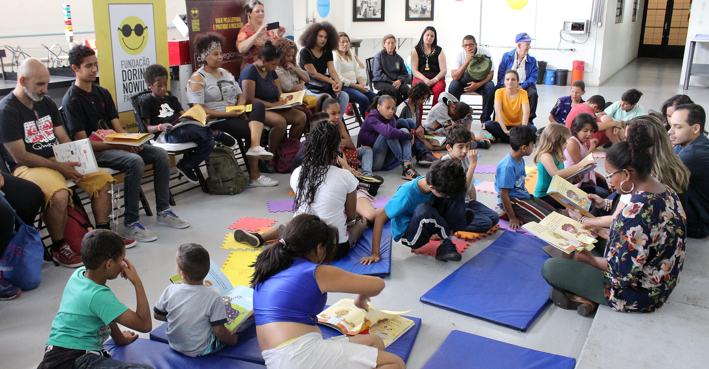 Descrição da imagem: foto de adultos e crianças, alguns sentados em cadeiras, outros em tapetes coloridos, com livros nas mãos. De frente para eles e do lado direito da foto estão duas moças e um rapaz. Eles estão sentados no chão, com livros abertos nas mãos. Fim da descrição.