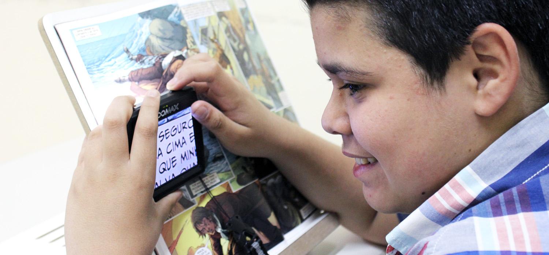 Descrição da imagem: foto de Jhonata lendo um livro com o auxílio da lupa eletrônica. Ele está de perfil, em um ângulo fechado em seu rosto, segurando o aparelho com as duas mãos sobre o livro. Fim da descrição.