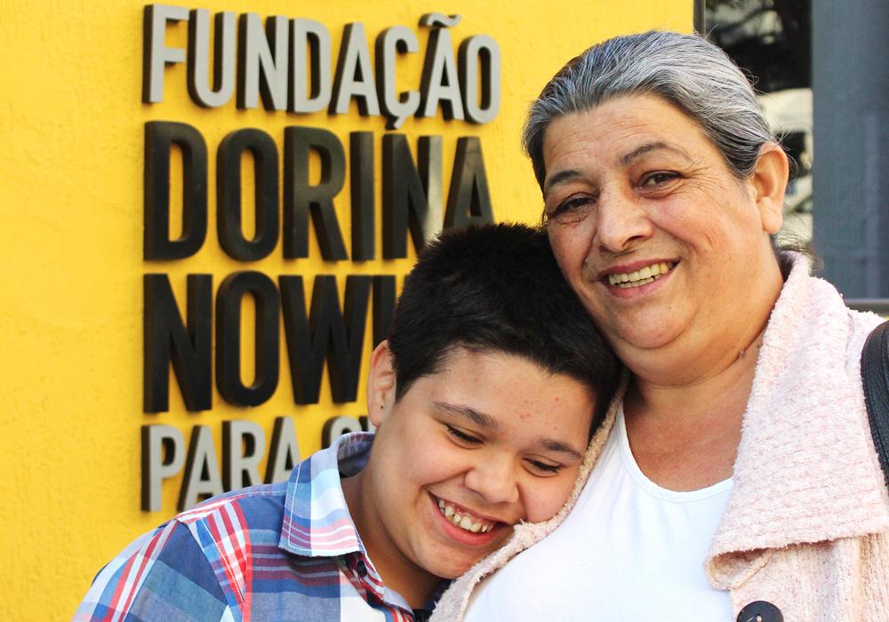 """Descrição da imagem: foto de Jhonata e sua mãe Ana Lúcia. Jhonata está sorrindo com a cabeça encostada no ombro da mãe, uma senhora de pele clara e cabelos grisalhos. Ela olha pra frente e sorri. Eles estão retratados do peito pra cima, na frente de uma parede amarela com um letreiro """"Fundação Dorina Nowill para Cegos"""""""