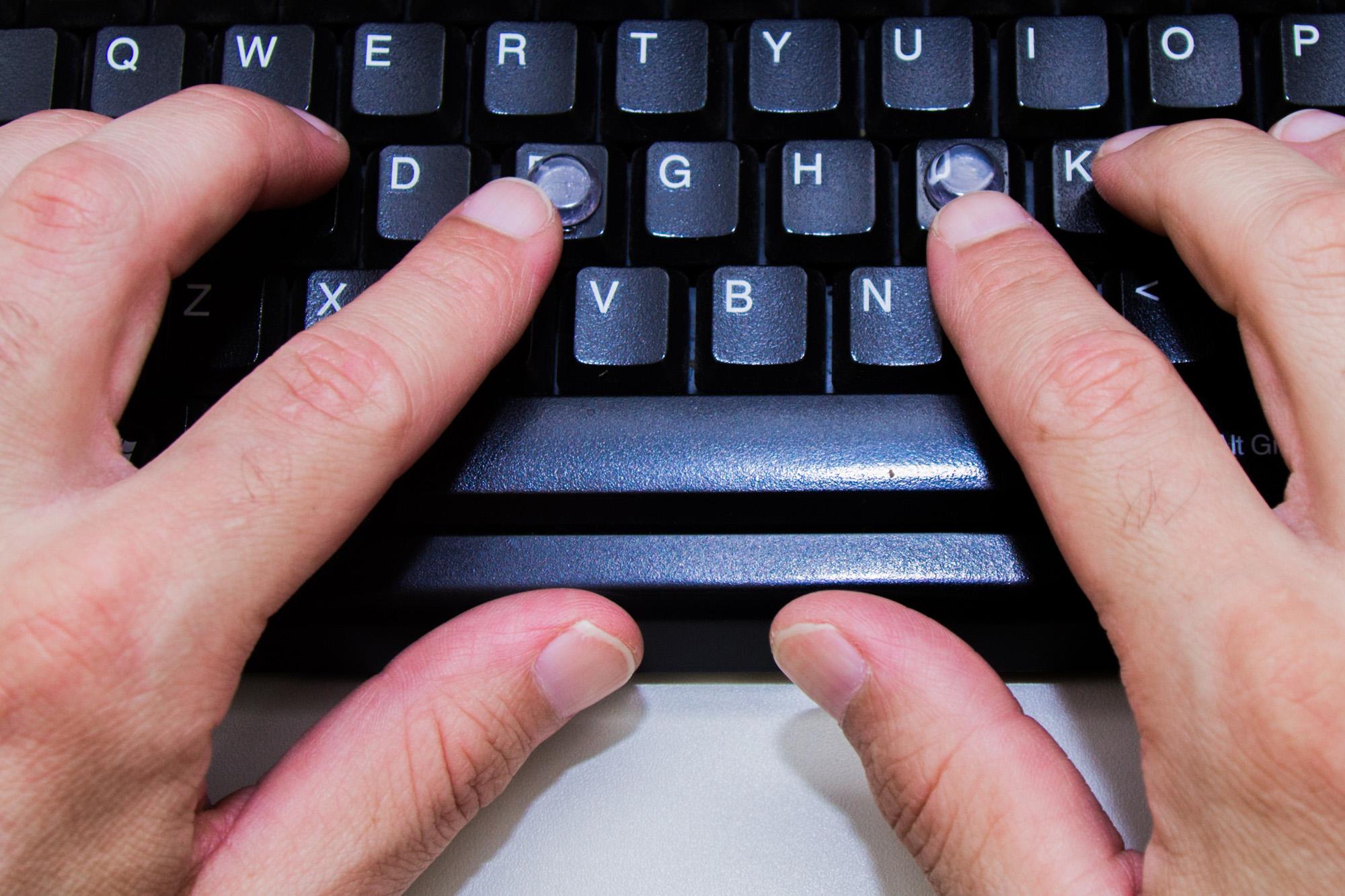 Foto de duas mãos sobre um teclado.