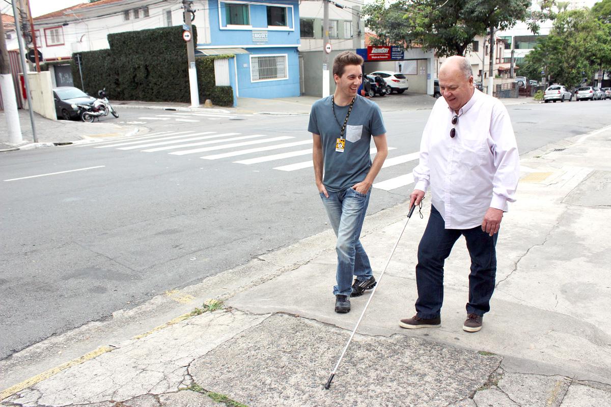Descrição da imagem: foto de Luiz e Fabrizzio caminhando por uma calçada. Eles estão sorrindo. Luiz usa bengala e olha em direção ao chão. Ao lado esquerdo há uma rua com alguns carros estacionados e uma faixa de pedestres. Fim da descrição.