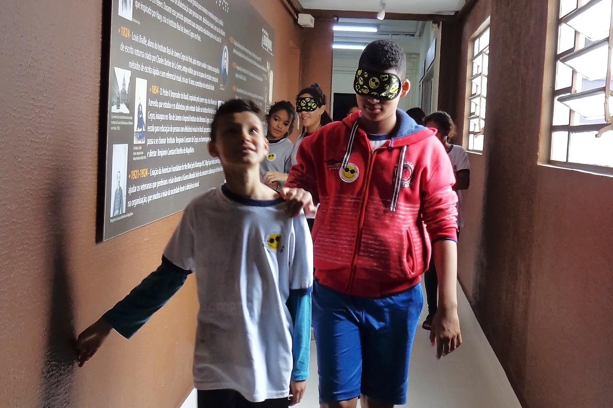 Foto de dois meninos em um dos corredores da Fundação Dorina. Um deles está vendado e com a mão no ombro do colega. Atrás deles há um grupo de crianças.