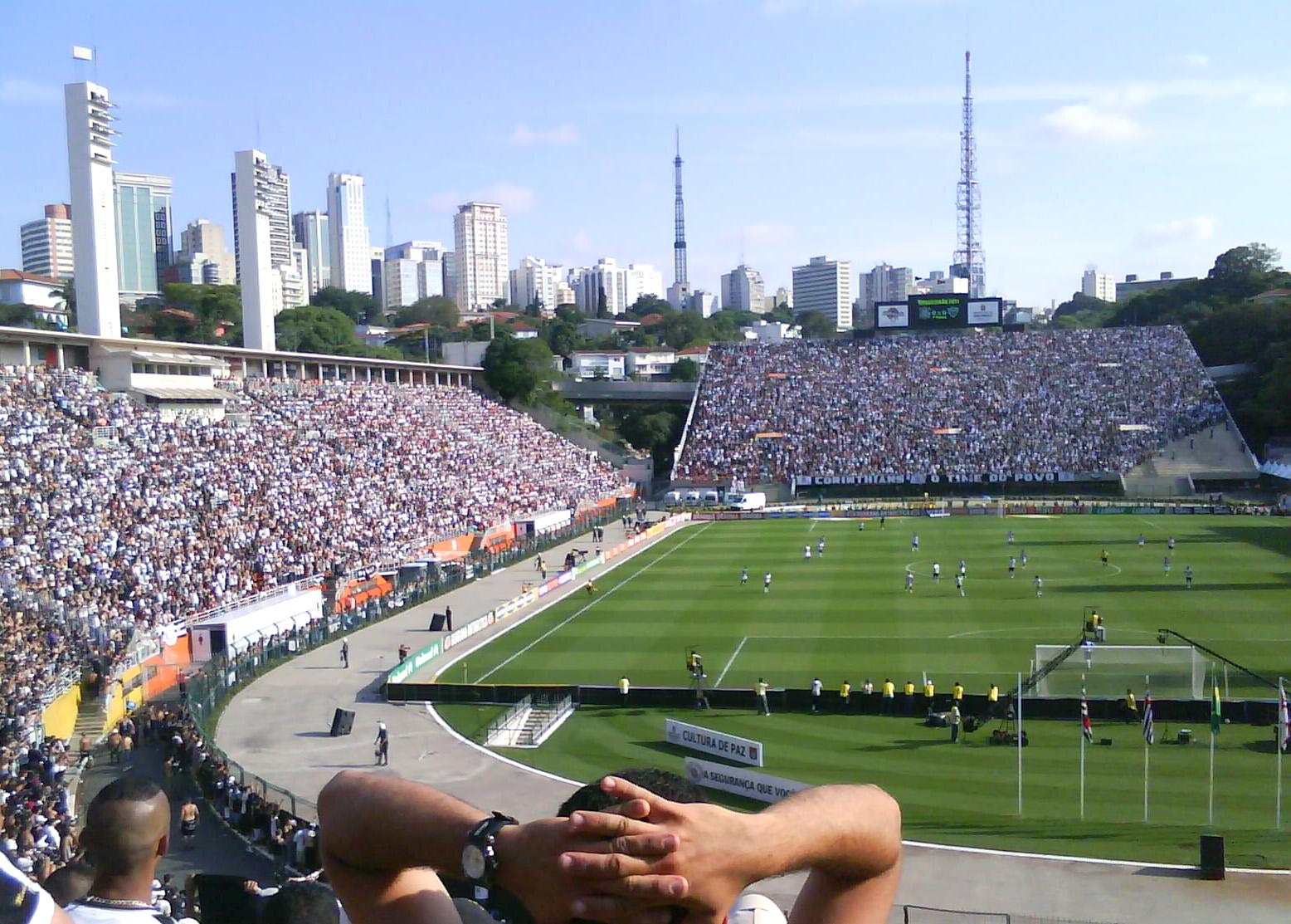 Descrição da imagem: foto do estádio do Pacaembu cheio pelo ponto de vista da arquibancada atrás de um dos gols. Em primeiro plano há um torcedor com as mãos na cabeça. Fim da descrição.