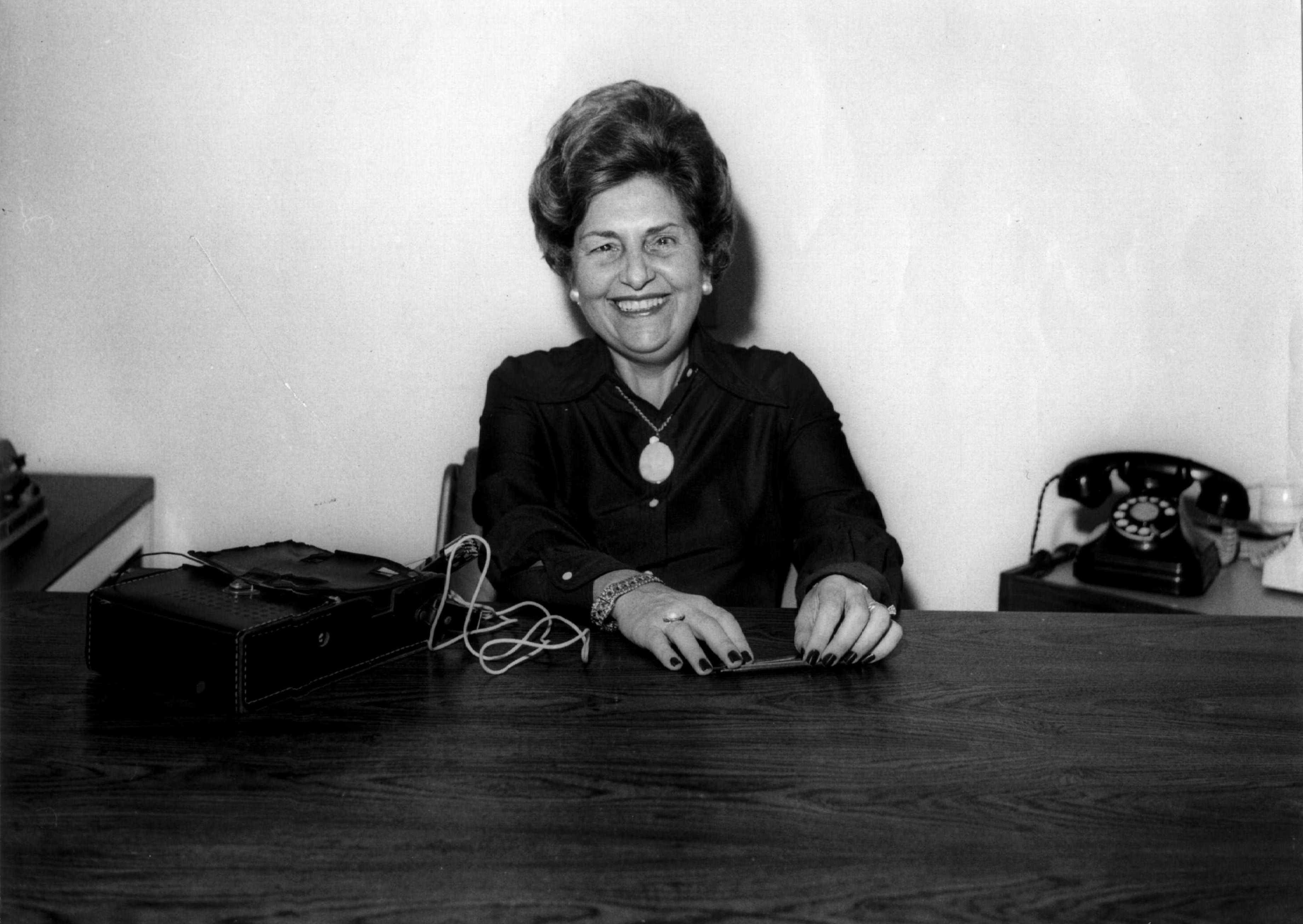 Imagem de Dorina Nowill jovem em preto e branco. Dorina está sentada em uma mesa sorrindo