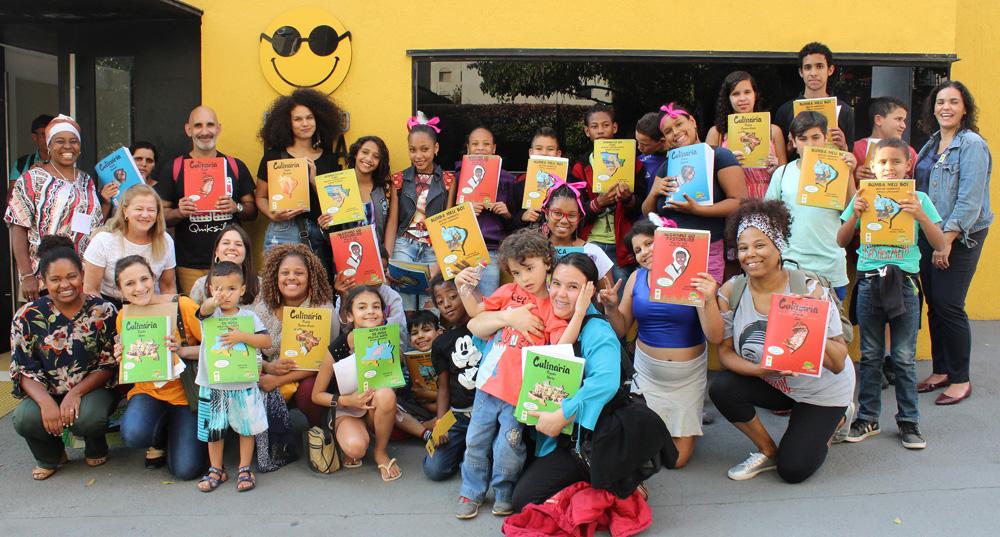 Descrição da imagem: foto de um grupo de crianças e adultos exibindo livros da Coleção Regionais. Eles olham pra frente e sorriem. Fim da descrição.