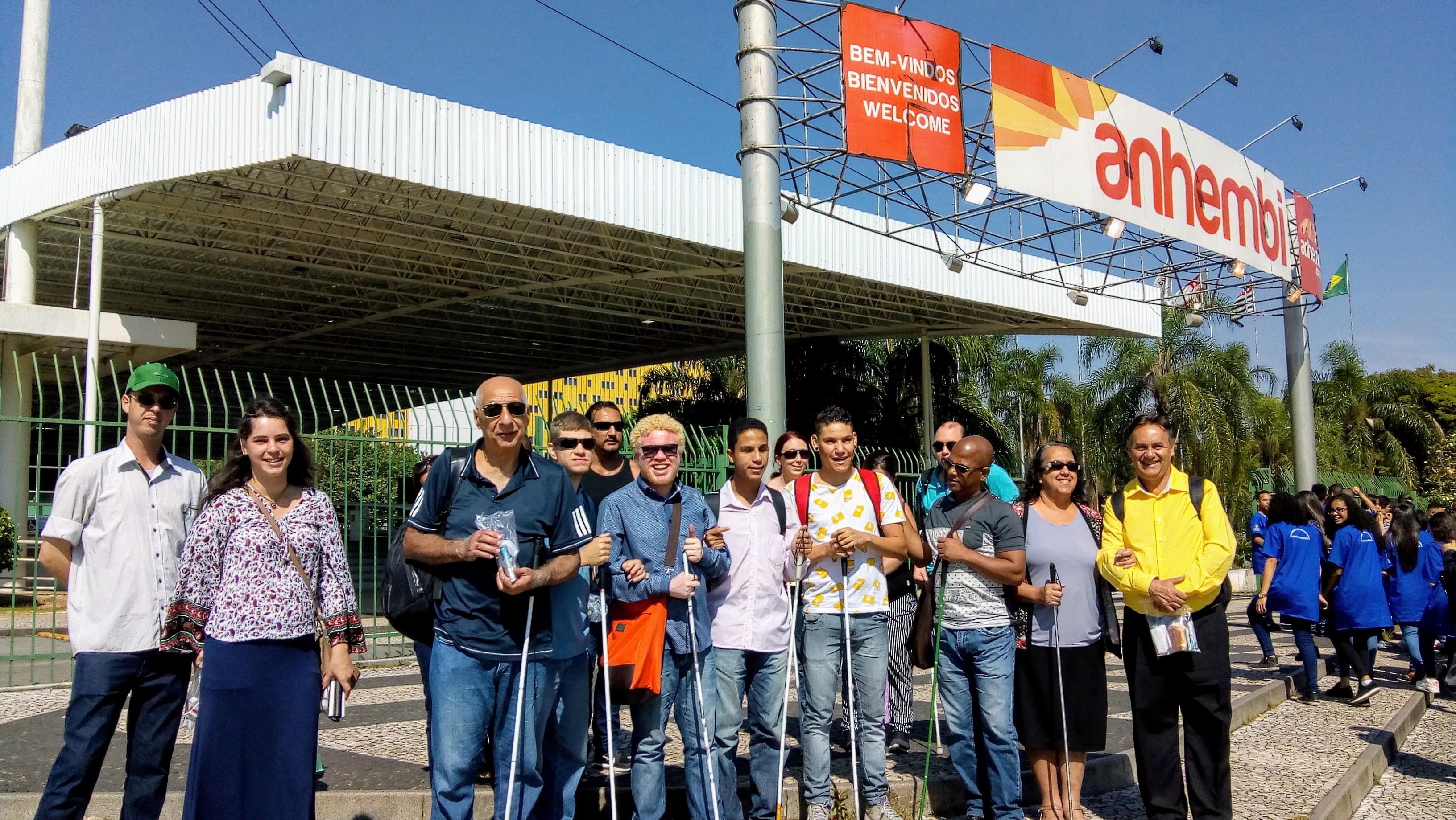 Foto de todos os alunos, ex-alunos e clientes em frente à entrada da Feira do Empreendedor. Eles olham pra frente e sorriem. Alguns seguram bengalas.
