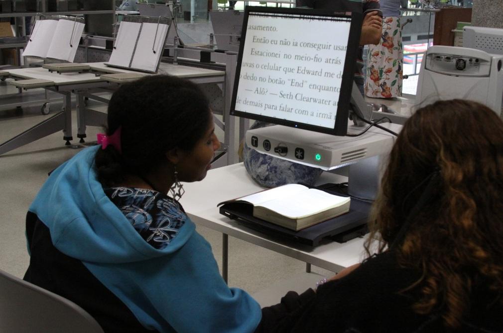 Descrição da imagem: foto de duas moças à frente de um monitor com lente de aumento digital, que exibe a página de um livro em papel. Ao fundo há mesas vazias da Biblioteca de São Paulo.