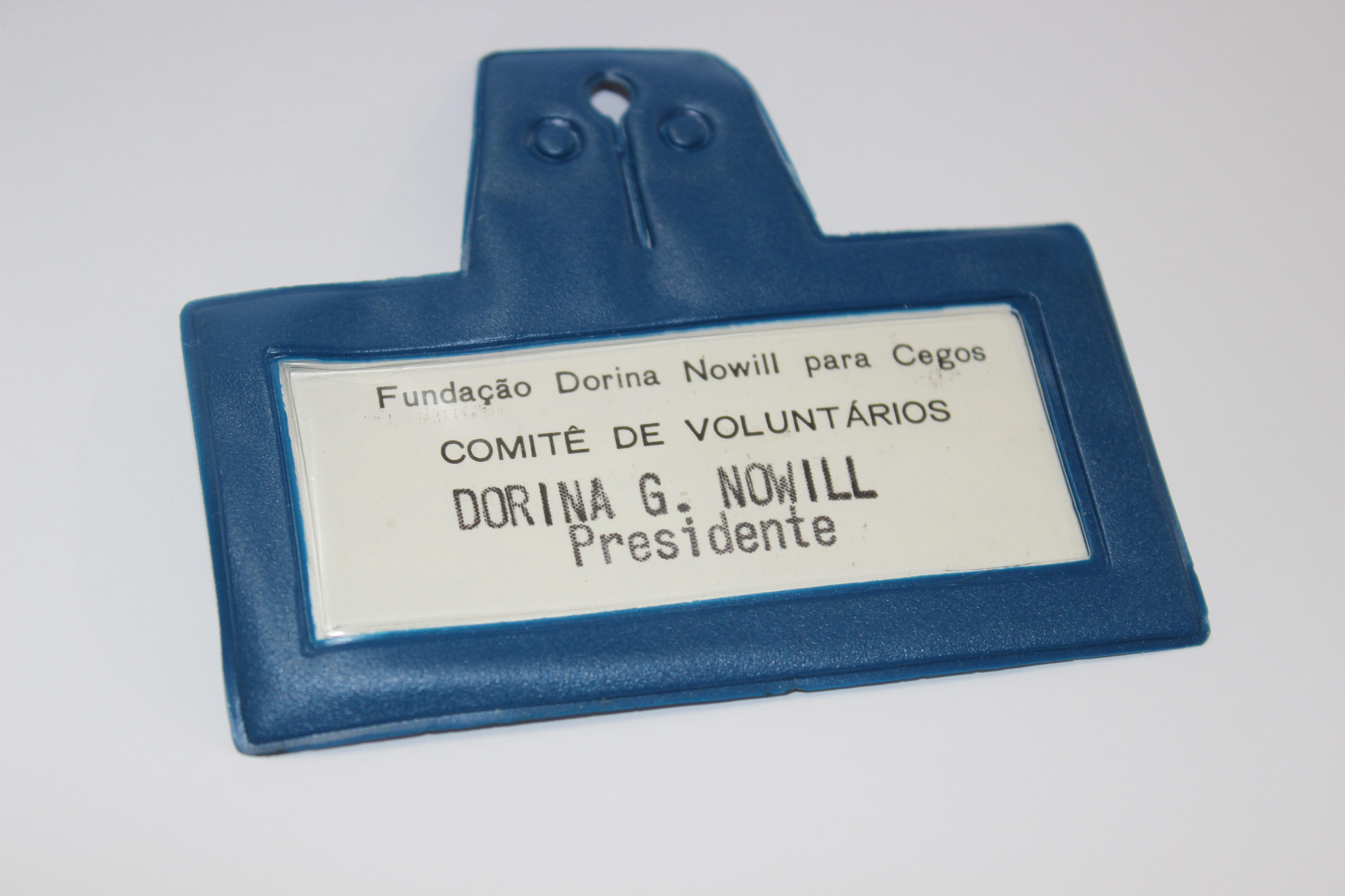 """Descrição de imagem: foto de um crachá, em fundo branco, e nele está escrito: """"Fundação Dorina Nowill Para Cegos. Comitê de voluntários. Dorina G. Nowill presidente""""."""