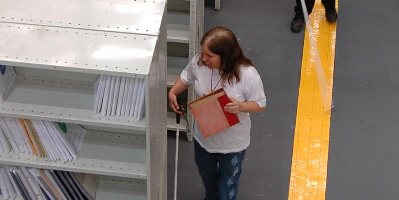 Descrição da imagem: foto de uma mulher ao lado de uma estante de livros da Biblioteca Louis Braille. Ela segura uma bengala numa mão e um livro de capa vermelha na outra. Ao lado direito é possível ver pernas de outra pessoa de bengala sobre piso tátil.