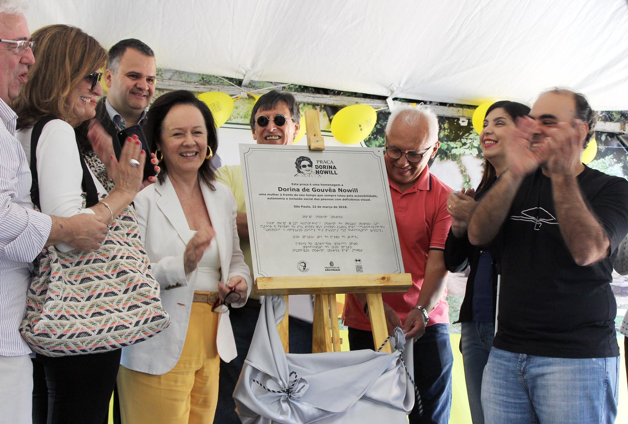 Descrição da imagem: foto de um grupo de nove pessoas em volta da placa em homenagem à Praça Dorina Nowill em um cavalete de madeira. Eles estão sorrindo e aplaudindo. Ao fundo há alguns balões amarelos.