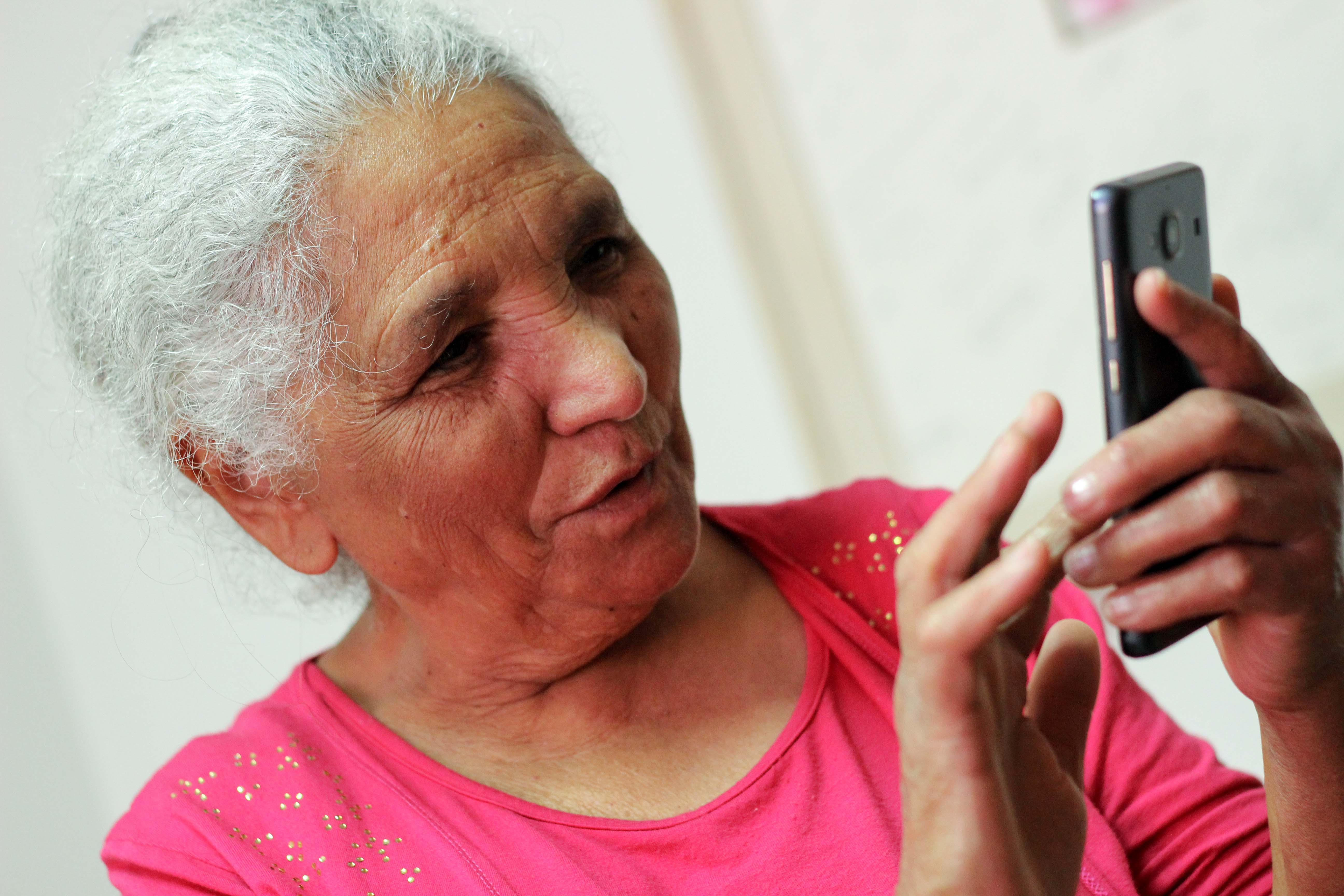 Descrição da imagem: foto de D. Maria tateando seu smartphone. Ela olha em direção ao aparelho em suas mãos.