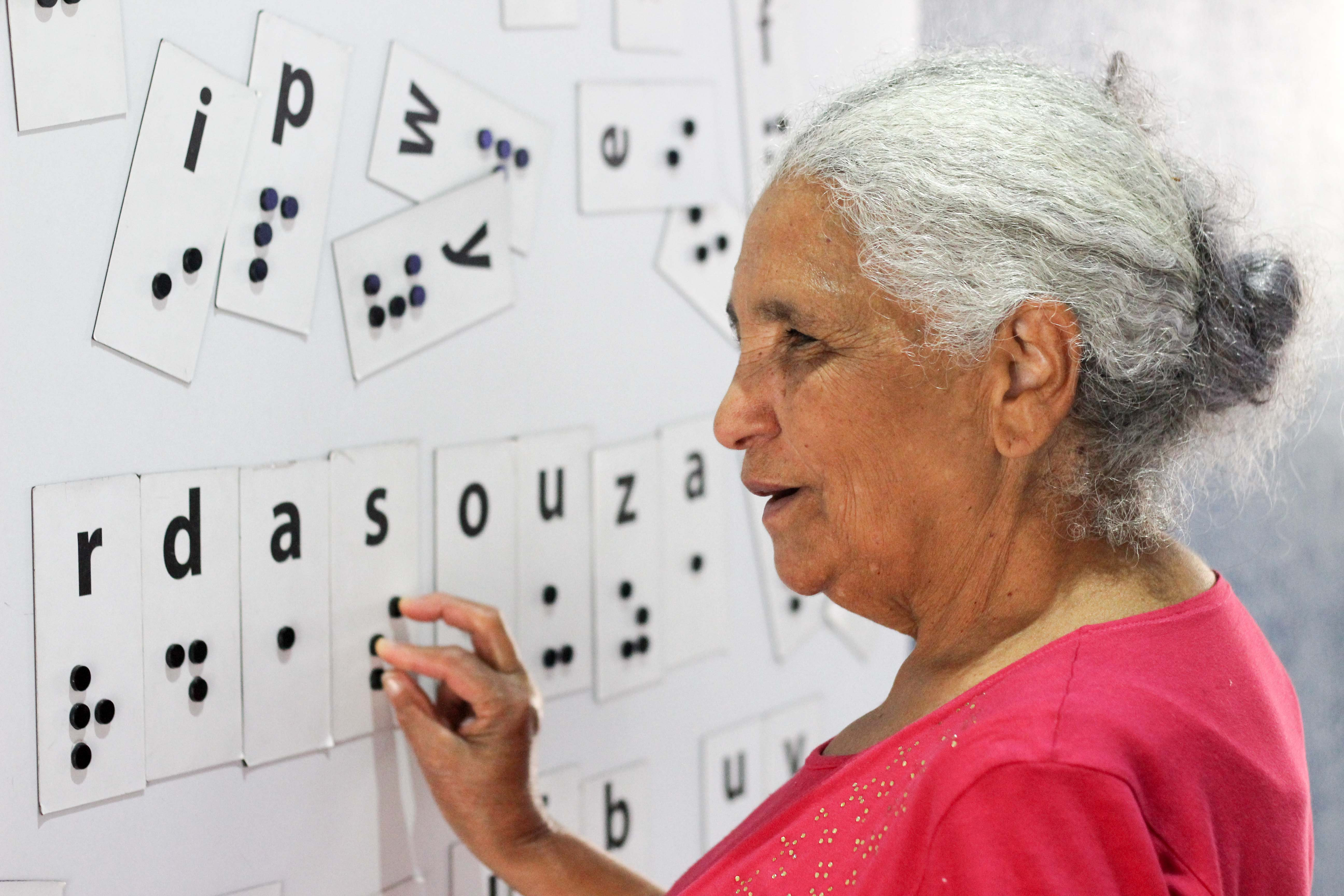 Descrição da imagem: foto de Dona Maria tateando um painel magnético com várias letras em braille embaralhadas. Ela está de perfil.