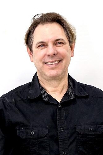 Descrição da imagem: foto frontal de Edson Defendi sobre fundo branco. Ele tem cabelos curtos, lisos e loiros, pele branca e olhos azuis. Está sorrindo. Ele usa camisa preta.