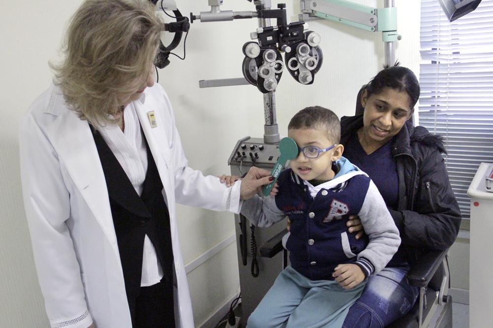 Descrição da imagem: foto de Marquinhos fazendo um exame oftalmológico. Ele está sentado no colo da mãe e segura o braço de uma profissional da Fundação Dorina, que o examina. Ela está de pé, cobrindo o olho direito de Marcos com uma haste de plástico verde.