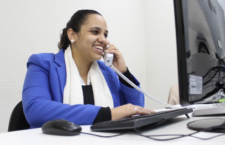 Descrição da imagem: foto de Stephani falando ao telefone numa mesa com computador. Ela está em meio perfil, olha em direção à tela e sorri.